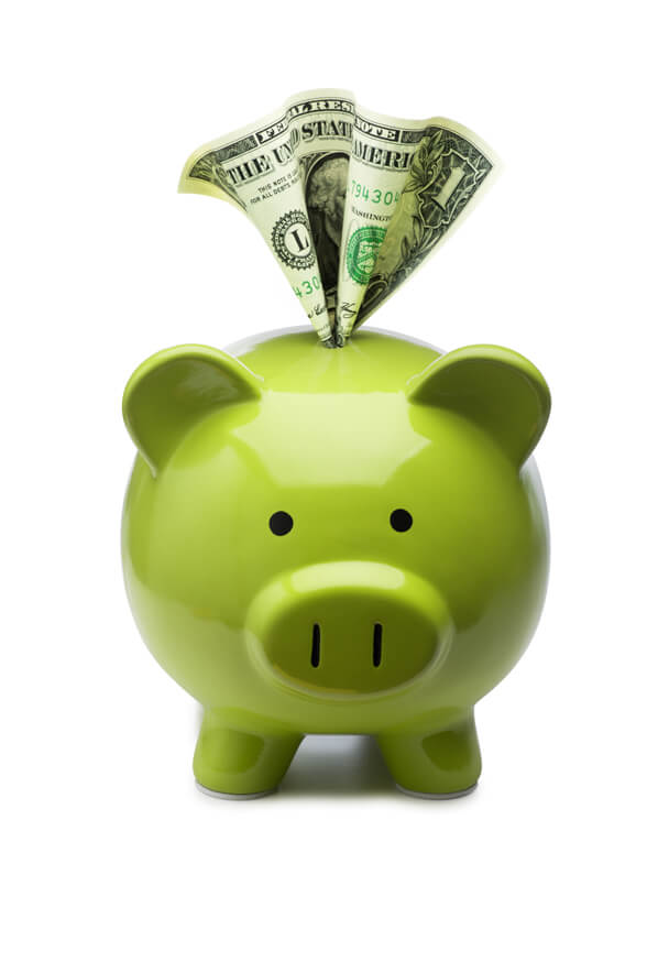 Green piggy bank with savings being added to it
