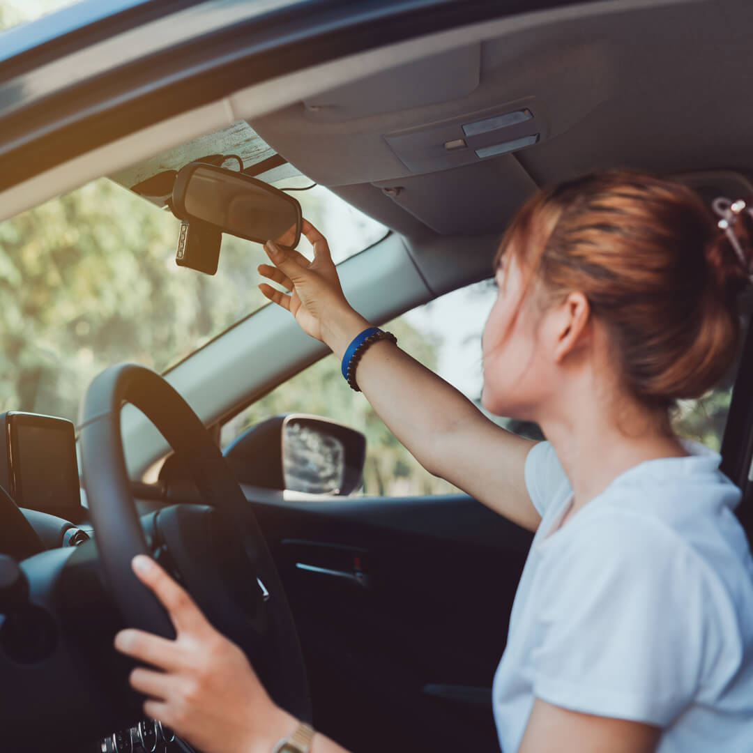 Young woman in her car, adjusting her rearview mirror and practicing defensive driving.